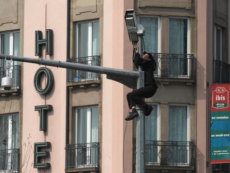 Juché sur un panneau routier, un protestataire tente de détruire une caméra de surveillance.