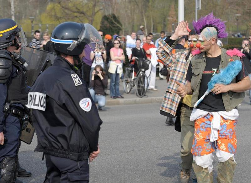 Ambiance plus détendue sur cette image. Ici, des manifestants déguisés en clowns font face à des policiers.
