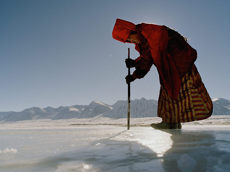 Cette femme du camp du roi tente, à l'aide d'un bâton, de briser la glace de la source.