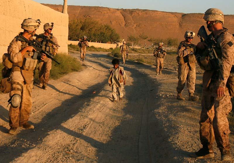 L'image est à double sens et pourrait à elle seule raconter la guerre menée en Afghanistan, avec ses excès et ses conséquences. Au milieu d'une colonne de soldats américains – des hommes du deuxième bataillon du 8e régiment de marines – et de militaires de l'Armée nationale afghane en patrouille dans la province d'Helmand, au sud-ouest du pays, un enfant marche en tirant son jouet. A-t-il été arrêté comme les canons des fusils d'assaut braqués sur lui semblent le confirmer ? En fait, la scène est commune en Afghanistan. L'enfant, comme de nombreux civils, ne fait que passer, indifférent à la guerre qui s'invite dans les rues de son village.