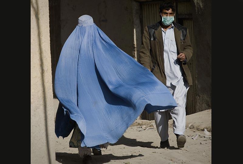 Un homme porte un masque de protection alors qu'il descend une rue dans le centre de Kaboul, mardi 3 novembre. Le gouvernement afghan recommande la fermeture de toutes les institutions pendant une période de trois semaines, conséquence de l'élévation soudaine de cas de grippe H1N1 et d'une première victime la semaine dernière.