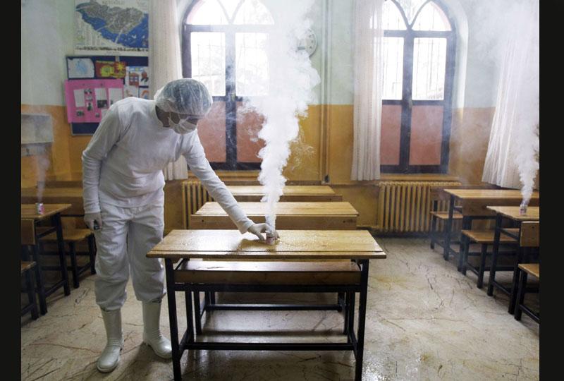 En Turquie, un ouvrier de la municipalité de Beyoglu, près d'Istanbul, utilise un désinfectant dans une salle de classe d'école primaire, pour éviter la propagation du virus H1N1, fin octobre.  Le ministère de la santé a indiqué que deux personnes sont décédées de la grippe cette semaine.
