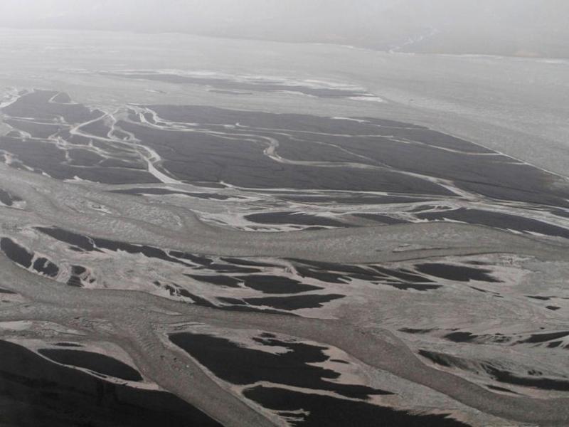 Outre le nuage volcanique, l'éruption souterraine survenue le 14 avril a provoqué la fonte du glacier, engendrant de fortes inondations. Les traînées grises sur la photo sont faites de cendres et de glace.
