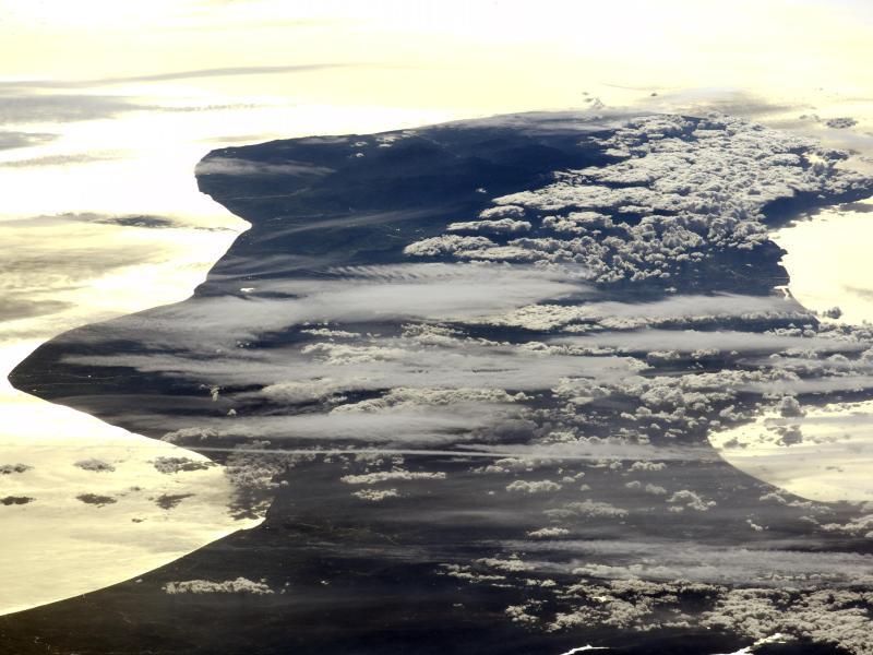 La Calabre (région du sud de l'Italie) encadrée par les mers ionienne et tyrrhénienne et déformée par l'angle rasant de prise de vue. Les reflets du soleil créent un effet miroir saisissant. La photo a été prise à bord de l'ISS alors qu'elle passait au nord-ouest de la Roumanie.