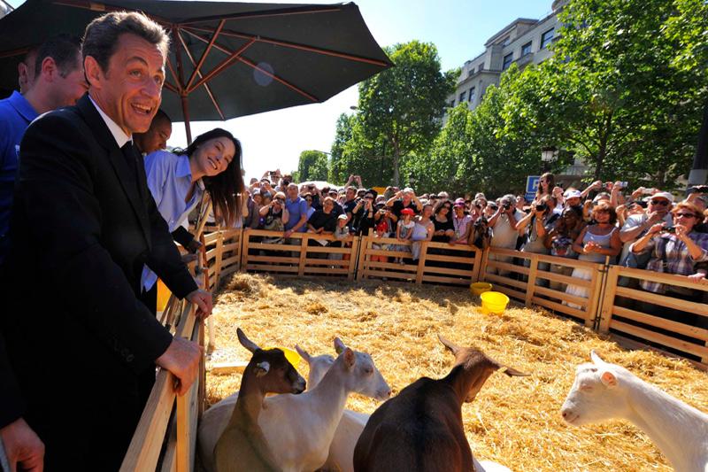 Nicolas Sarkozy et son épouse Carla Bruni-Sarkozy ont pris un bain de foule lundi sur l'avenue des Champs-Elysées transformée  en mini-salon de l'Agriculture avec enclos à bétail et parcelles végétales.