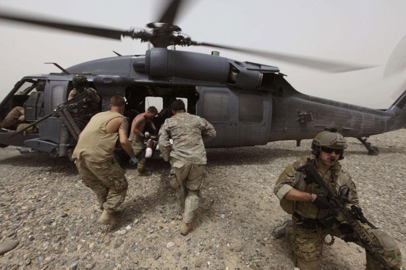 Aide. Mercredi 28 juillet, dans la province de Kandahar, en Afghanistan, ces militaires américains portent secours à un homme blessé afin de l'évacuer par hélicoptère en direction de l'unité de soin la plus proche.