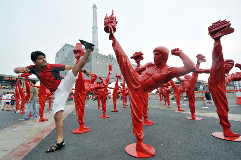 A l'exposition universelle de Shanghai, un touriste indien pose à côté des statues de Bruce Lee.