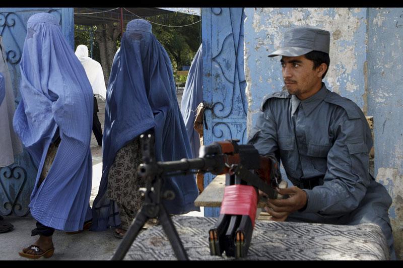 Samedi 18 septembre, à Jalalabad, en Afghanistan, ces femmes en burqa sortent d'un bureau de vote, alors qu'un policier monte la garde. Cette journée électorale s'est déroulée sous haute tension.