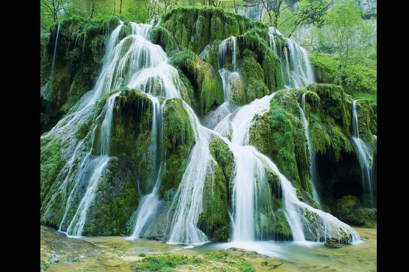 La Franche-Comté comme une cascade thaïlandaiseAu beau milieu d'une végétation luxuriante, dans un paysage lumineux et verdoyant,cette vertigineuse cascade jaillit sous l'objectif du photographe. A Erawan, en Thaïlande, des cascades semblables à celle-ci se répartissent sur 2 km de long. Près de Baume-les-Messieurs, en Franche- Comté, cette chute d'eau s'est formée dans le Dard, une rivière souterraine. Mauvaise nouvelle pour les amoureux du soleil, c'est quand il pleut que ce phénomène est le plus impressionnant...