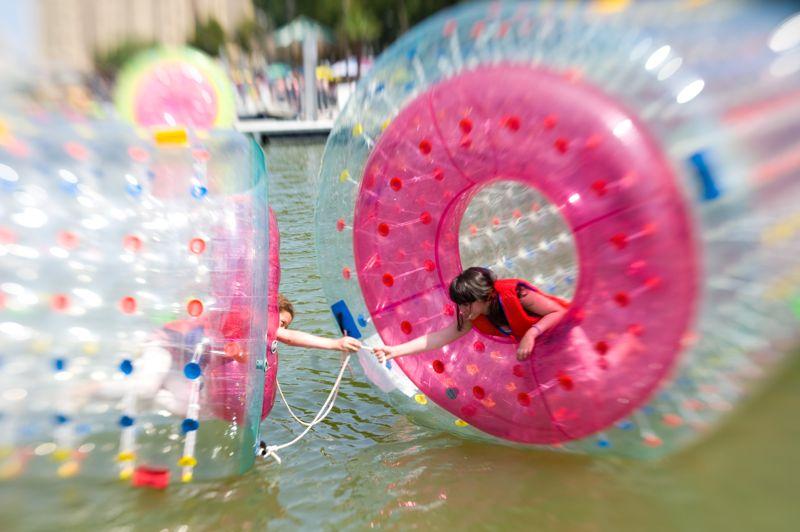 Sphères flottantes permettant aux enfants de rouler sur l'eau, bassin de la Villette.