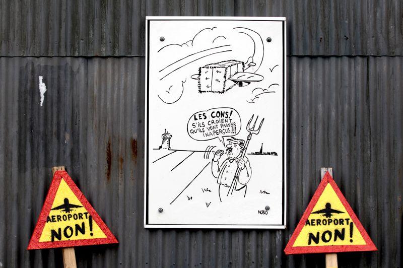 La vache rit. Des artistes locaux participent à leur façon aux actions militantes de la ZAD contre le projet de construction d'aéroport. Des panneaux de signalisation «AÉROPORT NON» et autres dessins humoristiques ornent les murs des habitations et les routes de la commune.