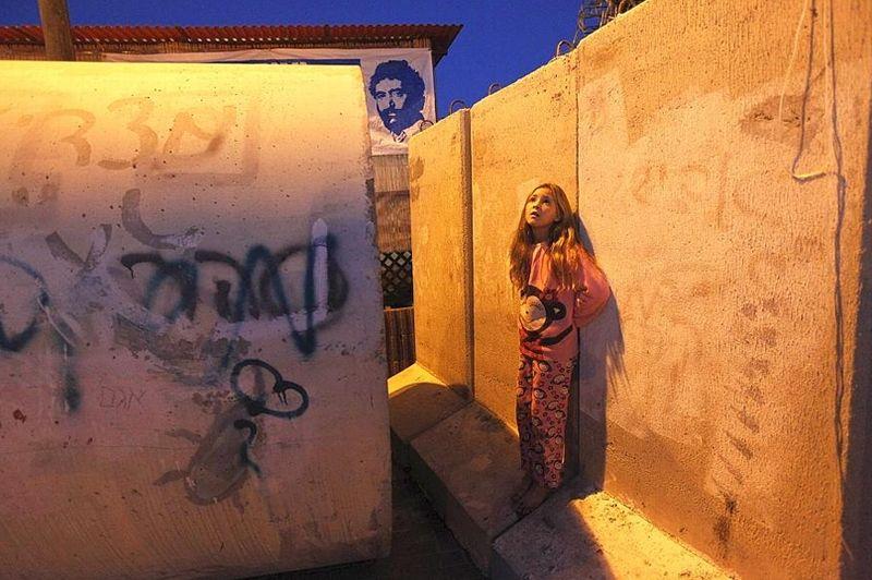A l'extérieur de son abri, une fillette israélienne regarde le ciel de Nitzan, près de Gaza, juste après une alerte rouge annonçant l'arrivée d'une roquette. La plupart des missiles tirés depuis Gaza sont interceptés par le système antimissiles d'Israël, le «Dôme de fer».