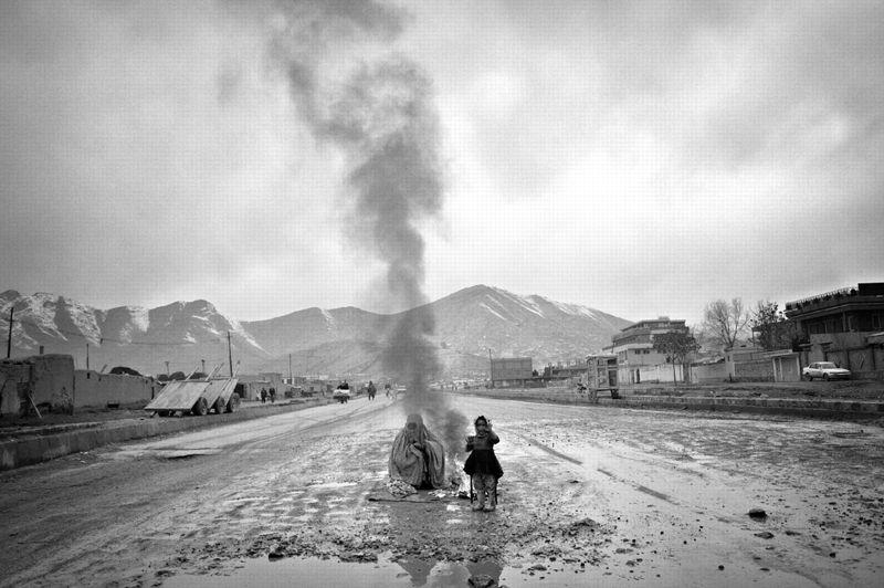 Kaboul, Afghanistan, février 2009. - Une femme portant la burqa et sa fille se réchauffent près d'un feu de camp, au milieu d'une route boueuse. Plus de 3,5 millions de réfugiés afghans sont revenus au pays après la chute des talibans, n'y trouvant souvent que des ruines.