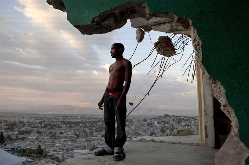 Port-au-Prince, Haïti, février 2011. - Un an après le séisme qui a ravagé son pays, un jeune Haïtien contemple le quartier de Fort National, l'un des plus sévèrement ravagés par la catastrophe.