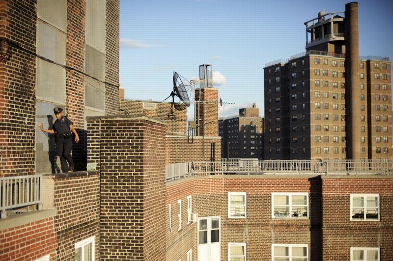 New York, États-Unis, juin 2009. - L'officier de police Olivero patrouille en équilibre sur le rebord d'un bâtiment du quartier de Mott Haven, dans le sud du Bronx. Le photographe Antonio Bolfo a lui-même travaillé au sein de la police new-yorkaise pendant deux ans, entre 2006 et 2008.