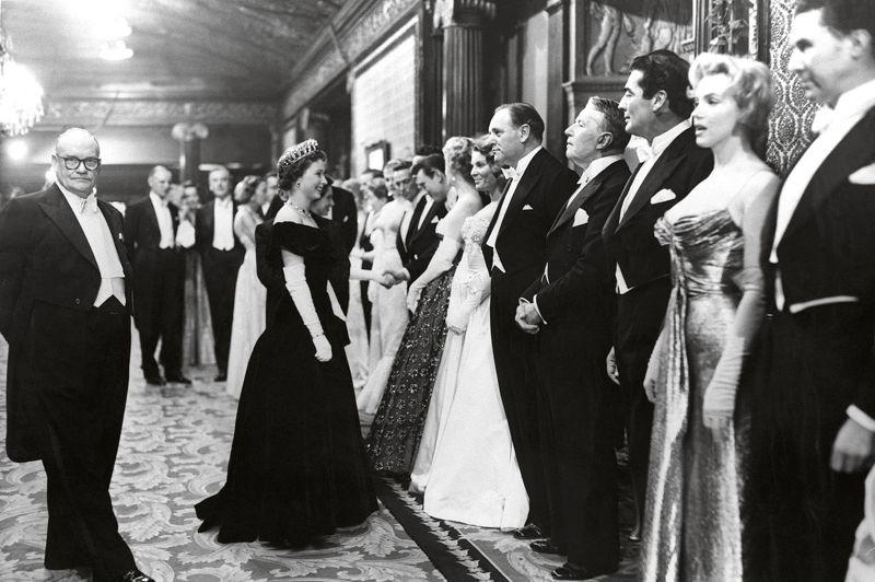 Lors de cette première de La Bataille du Rio de la Plata des réalisateurs Michael Powell et Emeric Pressburger en 1956, Elizabeth II n'a rien à envier aux stars hollywoodiennes qu'elle s'apprête à saluer. En bout de ligne, Marilyn Monroe anxieuse attend de rencontrer la reine. L'actrice était à Londres pour le tournage du Prince et la Danseuse, une mésaventure racontée cette année dans le film My week with Marilyn de Simon Curtis.