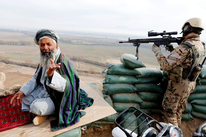 Dans la ligne de mire. L'effet de perspective donne à cette scène une atmosphère troublante et lourde. Pourtant, ce soldat allemand de la compagnie Alpha de la Quick Reaction Unit, l'œil rivé à sa lunette de tir, ne fait que suivre une procédure habituelle: vérifier qu'aucune menace ne pèse sur la zone. En position à un checkpoint du village de Qeysar Kheyl, près de Baghlan dans le nord de l'Afghanistan, son unité a été chargée de sécuriser une réunion entre des officiers de l'Otan et des responsables locaux, dont l'un des commandants de la police de la région, visiblement détendu et peu impressionné par les militaires qui l'entourent. Une scène ordinaire dans un pays toujours sous haute tension malgré le départ annoncé des troupes alliées fin 2014.