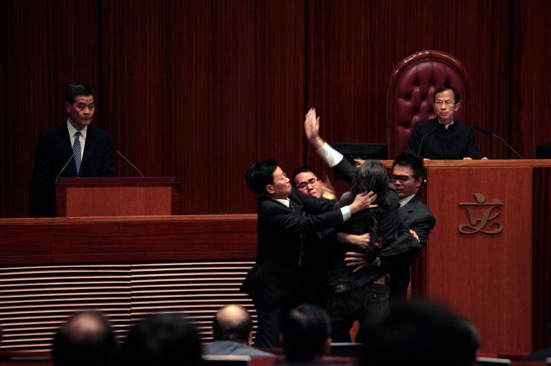 Stoppé net. Surnommé «Cheveux Longs», Leung Kwok-hung cet activiste marxiste (ici de dos) est connu pour son excentricité et ses actions spectaculaires. Mais cette fois, il a été freiné dans son élan, alors qu'il essayait d'approcher Leung Chun-ying, chef de l'exécutif de Hong Kong. Ce dernier comparaissait pour avoir réalisé des travaux illégaux dans une maison de famille. Un scandale qui pourrait le contraindre à démissionner, le sujet étant particulièrement sensible à Hong Kong, territoire surpeuplé où les travaux d'habitation sont très réglementés.