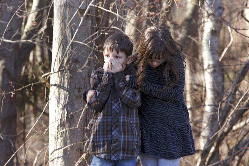 DÉCEMBREÉtats-Unis. Deux jeunes enfants attendent devant l'école primaire Sandy Hook à Newtown, dans le Connecticut, après une tuerie qui a couté la vie à 26 personnes le vendredi 14 Décembre. La grande majorité des victimes étaient des enfants âgées de 6 à 7 ans. Adam Lanza, 20 ans, l'auteur du massacre s'est ensuite donné la mort.