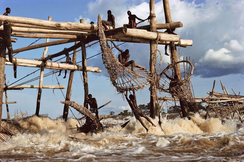 République démocratique du Congo, 1995. Dans les rapides du fleuve Congo, les pêcheurs Wagenia maintiennent une technique ancestrale à l'aide de nasses plongées dans les eaux bouillonnantes. Un mode de capture à haut risque. À la moindre erreur, les hommes peuvent basculer dans le vide et être emportés par le courant.