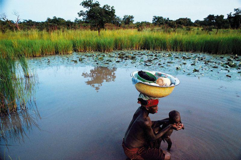 Comme une Vierge à l'Enfant. Cette jeune femme du Burkina Faso étanche la soif de son fils au bord d'un étang. Une scène d'une beauté immémoriale.