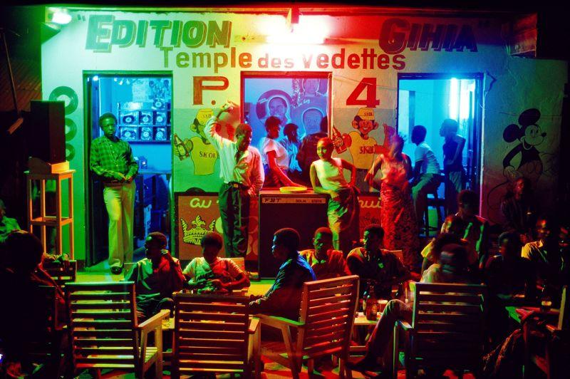 Zaïre, 1986. Une ronde de nuit à l'africaine, plongée dans la lumière fade des néons, dans un bar de Kikwit, la ville principale de la province de Bandundu.