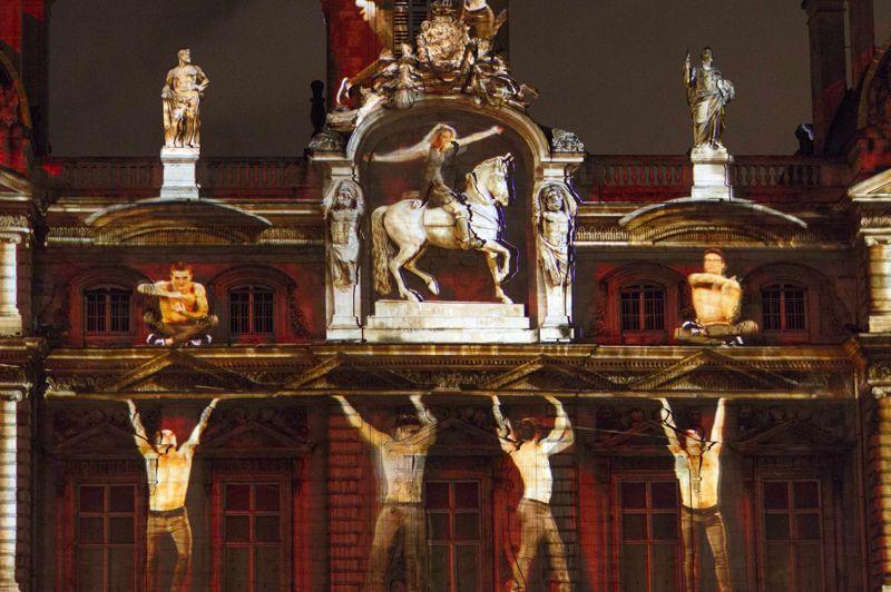 Les illuminations de Lyon, le 6 décembre 2012. La Fête des Lumières de Lyon, comme chaque année au mois de décembre, illumine la ville et l'habille de couleurs. Ici Highlights, création de l'agence Skertzo, semble, avec ses personnages monumentaux, donner vie à l'une des façades encadrant la place des Terreaux.
