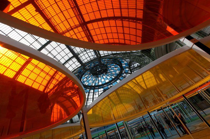 Couleurs sous la verrière. Paris, le 24 mai 2012. Pour la cinquième édition de Monumenta, c'est Daniel Buren qui investit l'immense espace qu'offre la nef du Grand Palais. Son but avec cette installation baptisée Excentrique(s), travail in situ est de «faire vibrer l'air et la lumière». Pari réussi.