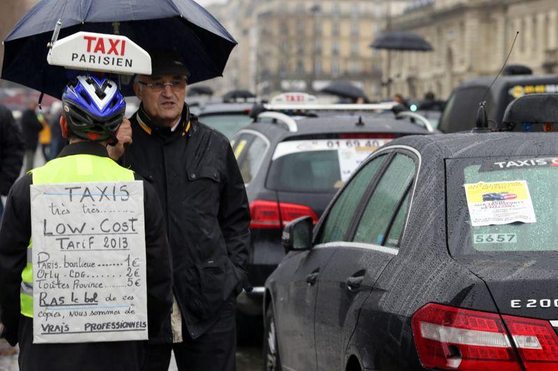 Un chauffeur de taxi parisien, portant un casque de vélo et une lumière de taxi sur la tête, déambule entre les voitures à l'arrêt avec un panneau des tarifs «très très low cost de 2013».
