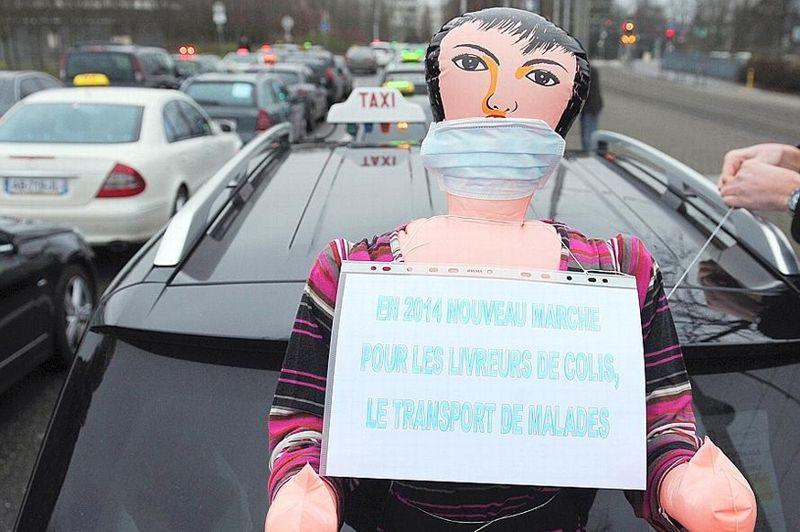 Du côté de Strasbourg, un chauffeur de taxi attache une poupée gonflable sur le capot de sa voiture. Sur la panneau: «En 2014 nouveau marché pour les livreurs de colis, le transport des malades».