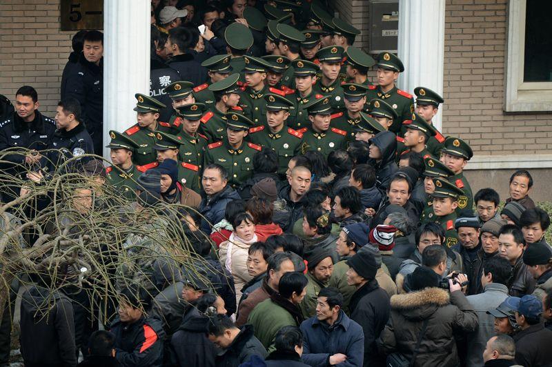 Disputes de fin d'année. Des policiers paramilitaires chinois protègent le siège d'une société de construction après la révolte d'employés qui réclament leurs primes de fin d'année. Ce type de conflits survient avant chaque nouvel an chinois, au moment où les travailleurs migrants s'apprêtent à rejoindre leurs familles.