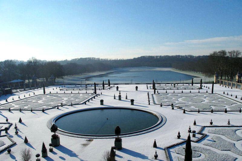 Le château du froid Soleil. Figé dans la poudreuse, le parc du château de Versailles étincelle sous le froid soleil d'hiver. Fermés au public pendant le week-end, en raison des fortes chutes de neige qui ont paralysé une large partie de la France, les jardins, comme les châteaux de Trianon et l'ensemble du domaine, sont restés drapés dans leur manteau immaculé. Un voile blanc qui a révélé comme rarement les lignes pures du jardin imaginé par Le Nôtre pour Louis XIV. Comme gravés à l'eau-forte, les moindres détails des massifs apparaissent dans leur beauté classique. Sertis par la neige et la ligne sombre des arbres, les bassins gelés reflètent à l'infini la douce lumière du ciel. Voici Versailles dans toute sa majesté.