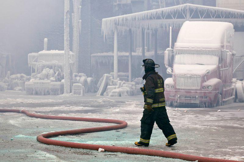Les bâtiments et les véhicules se trouvant à proximité du feu semblent avoir subi les assauts d'un blizzard.