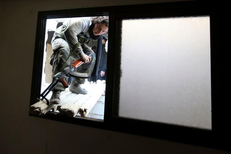 Les combattants de l'ASL entrent dans une maison sur la ligne de front dans le quartier d'Arabeen.
