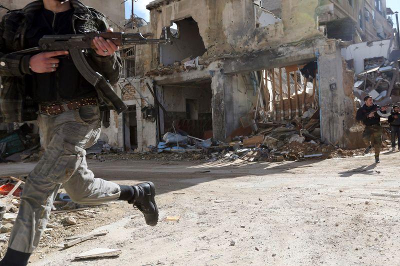 Des membres de l'unité Fateh-al-Sham traversent en courant une rue du quartier de Harasta.