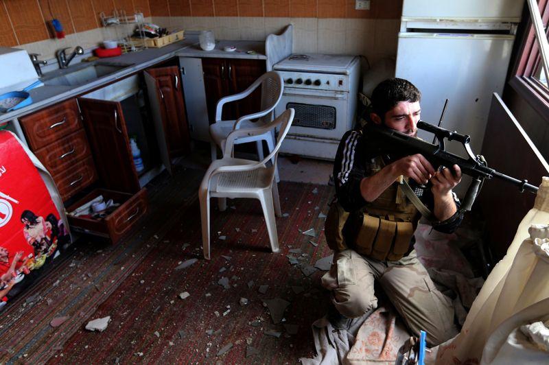 Un combattant de l'unité Sadik, appartenant à la brigade Tahrir-al-Sham de l'ASL, tirent avec son fusil de précision Dragonov lors d'intenses combats à Mleha dans la banlieue de Damas.