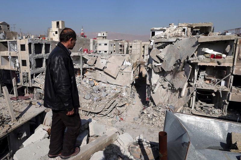 Un habitant de Douma, située à une dizaine de kilomètres de la capitale syrienne, observe les bâtiments détruits par l'aviation syrienne.