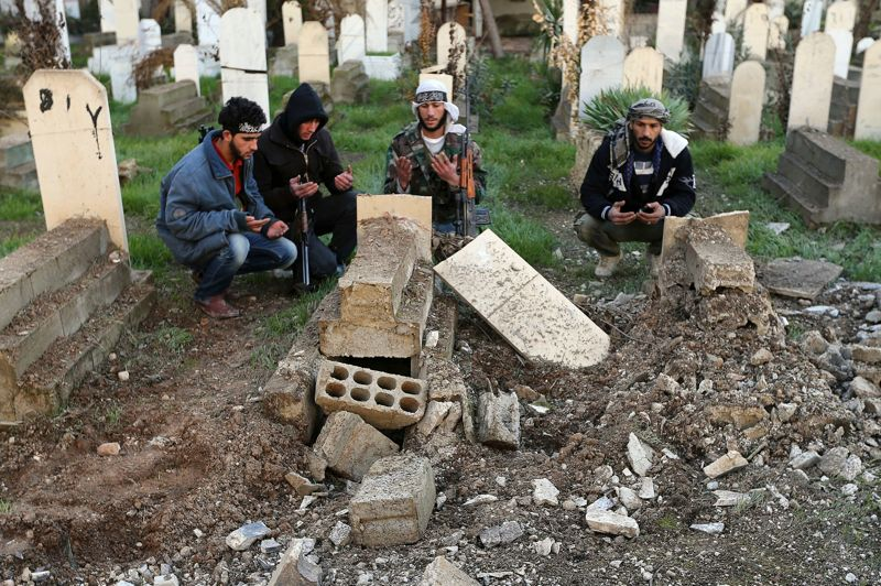 Des combattants de l'ASL prient autour d'une tombe endommagée par des tirs de mortiers à Mleha.
