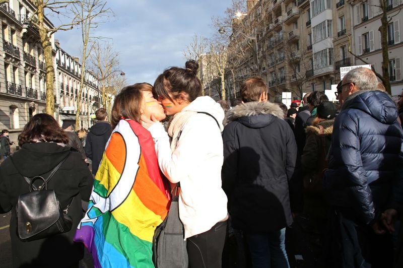 Deux jeunes femmes, dont l'une est entourée dans un drapeau aux couleurs de l'arc-en-ciel, symbole de la cause homosexuelle, s'embrassent pendant la manifestation.