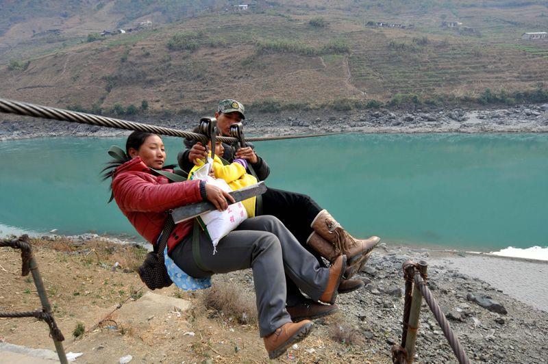 Traversée. Pour se rendre sur l'autre rive du fleuve Nujiang, un des grands fleuves du Sud-Ouest de la Chine, ces résidents de Shuangmidi, dans la Province du Yunnan, doivent utiliser cette tyrolienne. Sans elle, ce village isolé géographiquement entre de hautes montagnes et des fleuves qui coulent entre les pics, resterait coupé du monde. Aujourd'hui pourtant, ce mode de transport traditionnel est progressivement remplacé par des ponts suspendus, en bois et en chaîne métallique.