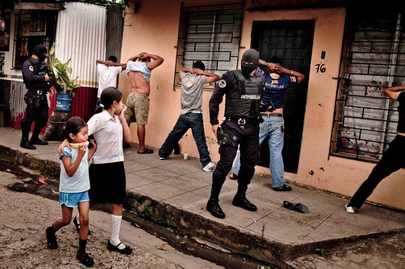Les yeux dans les yeux. Un bras sur l'épaule de sa petite sœur, cette fillette un peu inquiète échange un long regard avec l'un des hommes cagoulés de la brigade anti gang de la police du Salvador en plein contrôle d'identité. Une scène de rue presque banale dans la ville de San Salvador, gangrenée par la violence des bandes rivales qui s'affrontent chaque jour pour un bout de trottoir, une porte cochère ou un lieu de vente de drogue. Le visage masqué, pour leur propre sécurité, les policiers cherchent des armes ou des tatouages spécifiques qui pourraient indiquer l'appartenance de ces jeunes gens à un gang. Cette image, à la fois choquante et profondément humaine, vient de recevoir un World press Photo 2013 dans la catégorie «Vie quotidienne».