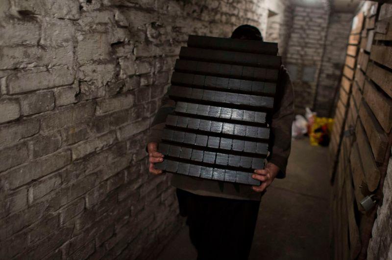 Il porte son fardeau de briques noires , tantôt directement dans les appartements des consommateurs, tantôt, comme ici, dans les caves des immeubles.