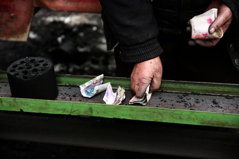 Notre homme compte ses yuans, règle le montant de son chargement avant d'aller le vendre. L'utilisation du charbon comme combustible domestique est une pratique très répandue dans les zones rurales.