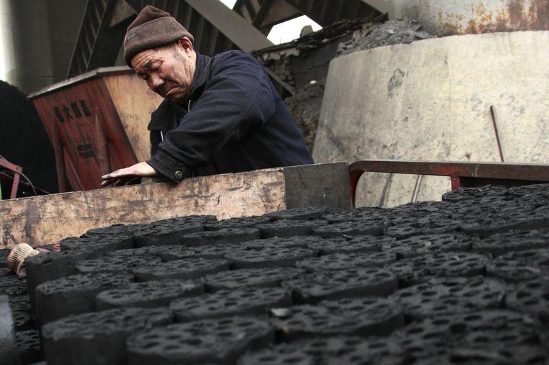 Ce travailleur chinois range le minerai aggloméré dans son cyclopousse.