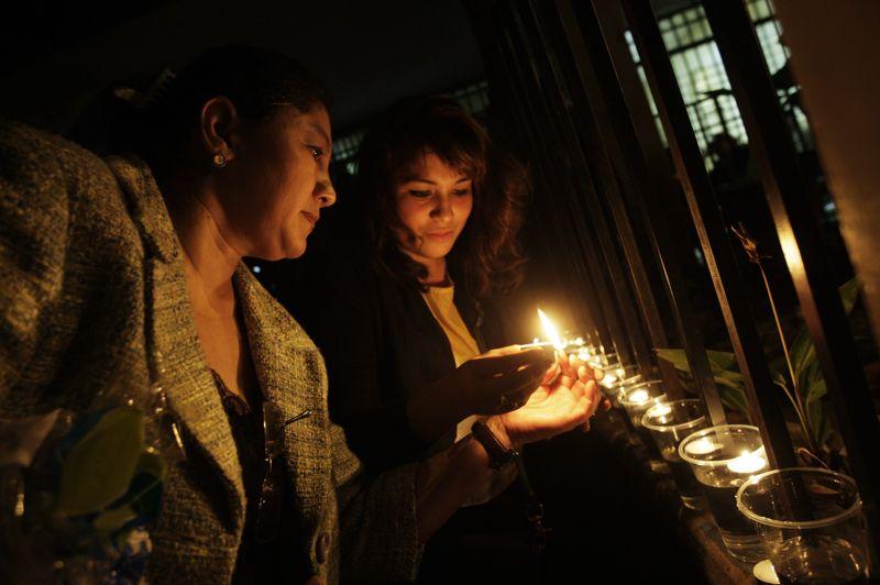 Des veillées sont organisées dans tout le pays. Deux femmes allument ici des bougies dans une école de Tegucigalpa. Les autorités ont décrété sept jours de deuil et des funérailles nationales sont prévues vendredi.