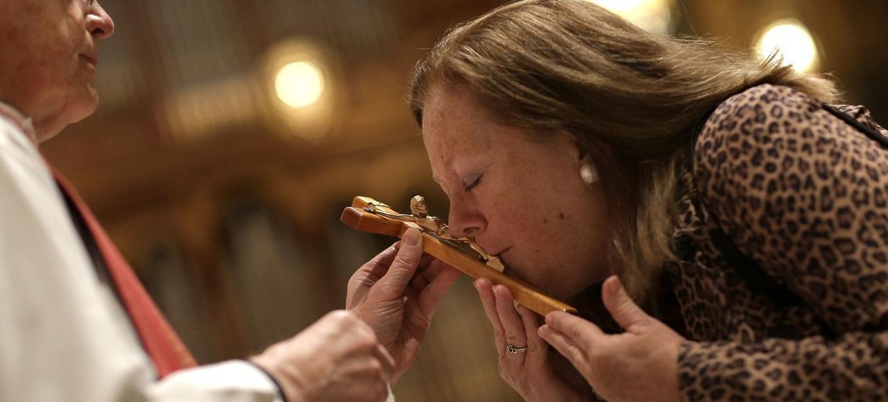 Une femme embrasse la croix de la communion de la messe du vendredi saint, en avril dernier, à la cathédrale St Matthews de Washington.