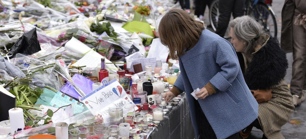 Une petite fille rend hommage aux victimes des attentats du 13 novembre, place de la République à Paris.