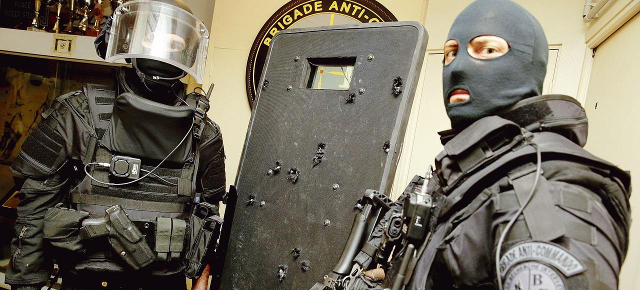 Des membres de la BRI montrent les impacts des balles sur leur bouclier de protection au Bataclan.