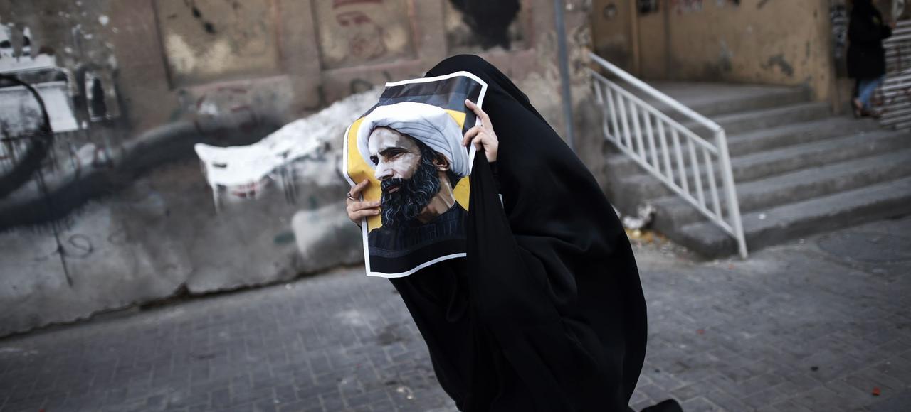 À Bahreïn, une femme porte un portrait du dignitaire chiite Nimr al-Nimr, exécuté Arabie saoudite.
