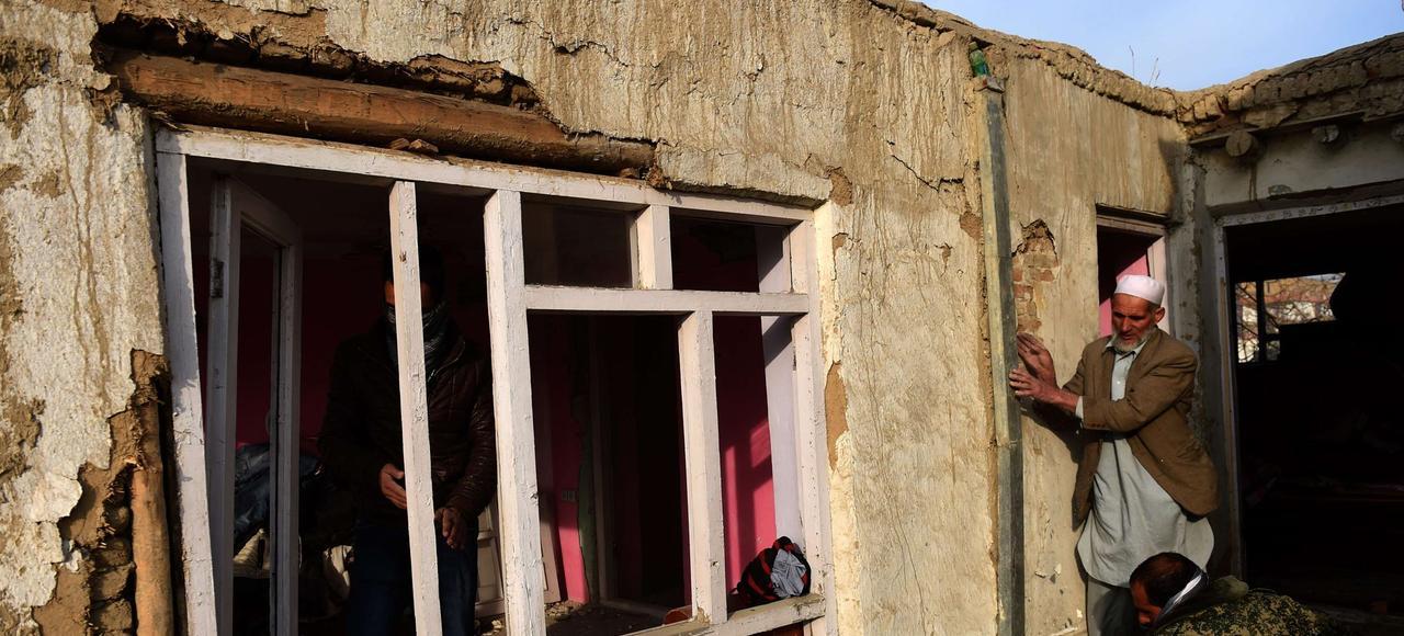 À Kaboul, après un attentat-suicide visant un restaurant français fréquenté par des étrangers, le 2 janvier 2016, des voisins évaluent les dégats causés à leur habitation.